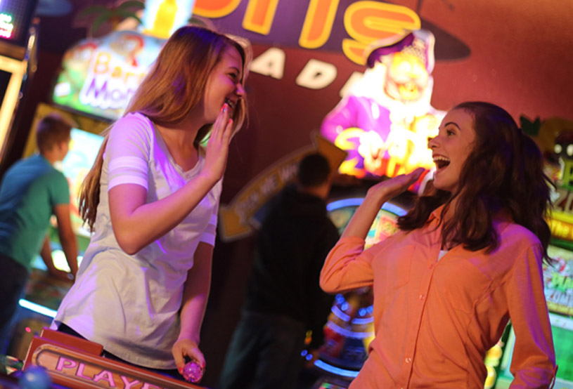 Girls high-five each other at the arcade
